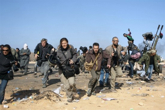 Paul Conroy / Reuters  Journalists, including New York Times photographers Tyler Hicks (right in glasses) and Lynsey Addario (far left), run for cover during a bombing run by Libyan government planes at a checkpoint near the oil refinery of Ras Lanuf on Friday, Mar. 11. Hicks and Addario, along with NYT correspondents Stephen Farrell and Anthony Shadid, were reported missing near lines of Muammar Gaddafi's advancing forces two days ago, the NYT announced on Wednesday.