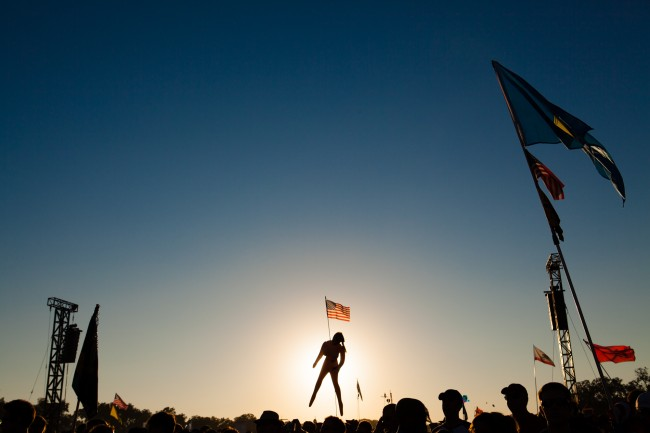 The silhouette of a blow up doll floats above the crowd at a music festival in Texas.