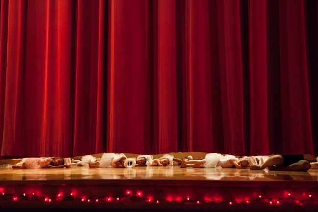 A troupe of ballerinas wait for the curtain to rise before their first dance recital.
