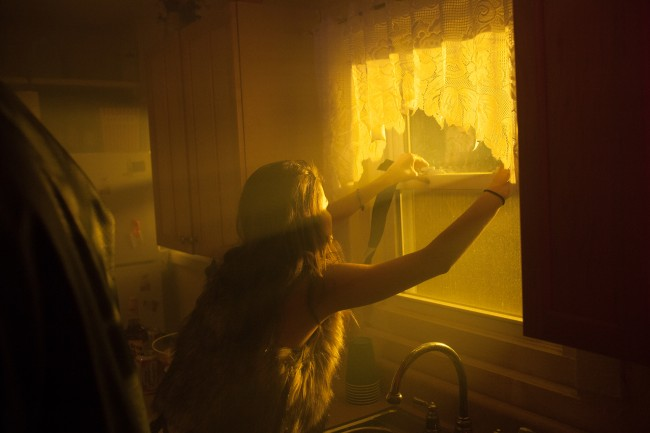 A woman opens a window on the set of a music video.