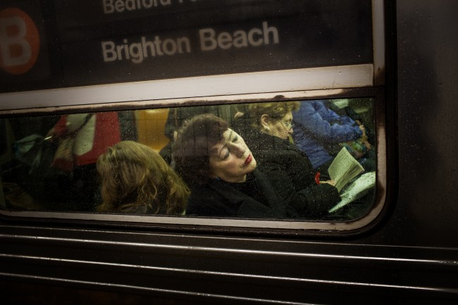 A woman sleeps on the B train on an early, rainy morning in Chinatown, New York City.