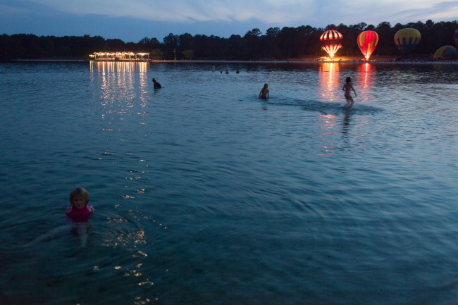Children play in a lake during a hot air balloon festival.