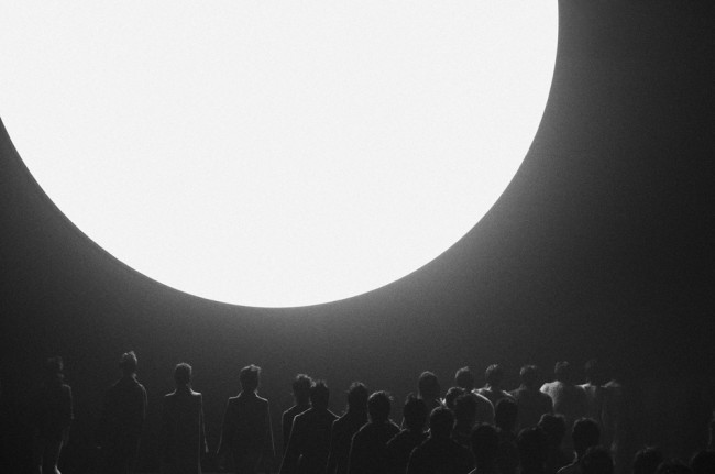 "We were commissioned by TIME Magazine to document New York Fashion week. This is one of our favorite photographs, shot at the Marc Jacobs Fall/Winter 2013 show. The image depicts models walking towards a large indoor ""sun"" installed at the venue, referencing artist Ólafur Elíasson's weather project."