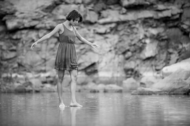 This was casual photo I took while exploring an old rock quarry with a friend. She was wading through the water when she found a rock to stand on that was just below the surface, making for a very surreal moment.