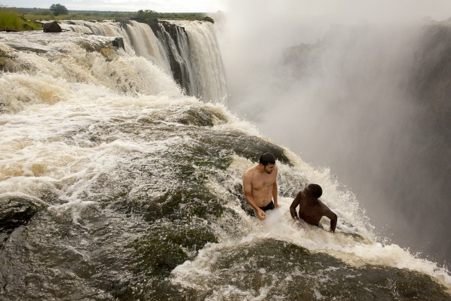 "These two maniacs are in a ""safe"" naturally formed pocket at the top Victoria Falls in Zambia – near the Devil's Pool. I still get dizzy just looking at this."