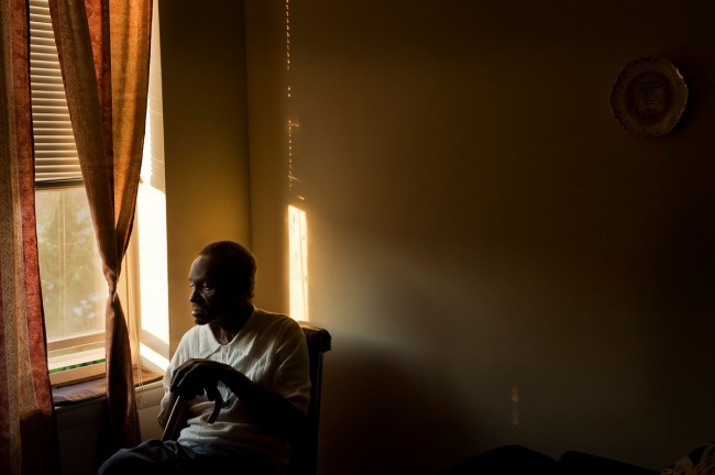 An elderly man sits by the window in his home after being robbed for his social security money in East Baltimore.  This was taken during a series of ride-alongs with the Baltimore City Police.