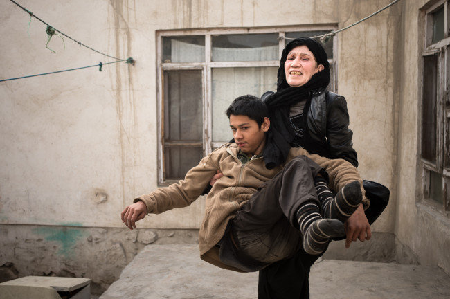 Kabul, Afghanistan. Barialy is now eighteen and becoming too heavy for his mother, Zarghona, to carry.