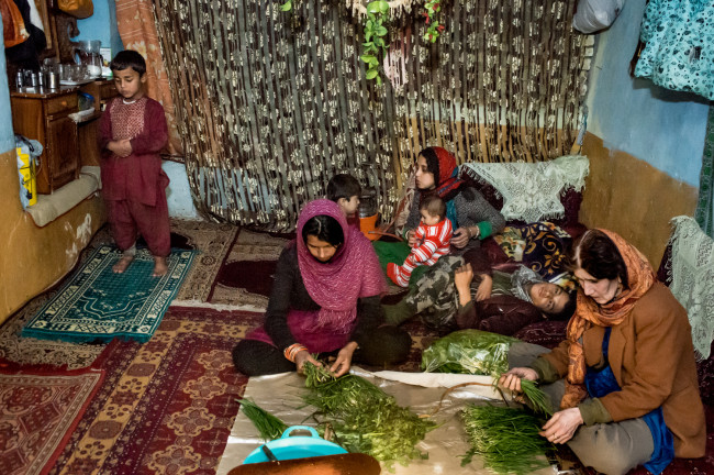 Zarghona and Gulali prepare diner for the family while her grandson prays.