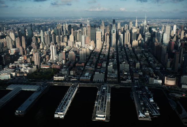 Aerial view of Midtown Manhattan and the Hudson River shoreline in the late afternoon.