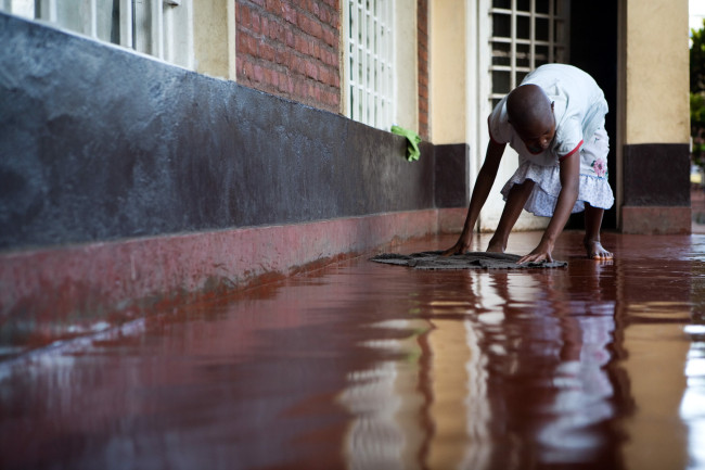 Masengesho mops the floors at her family's apartment after school.