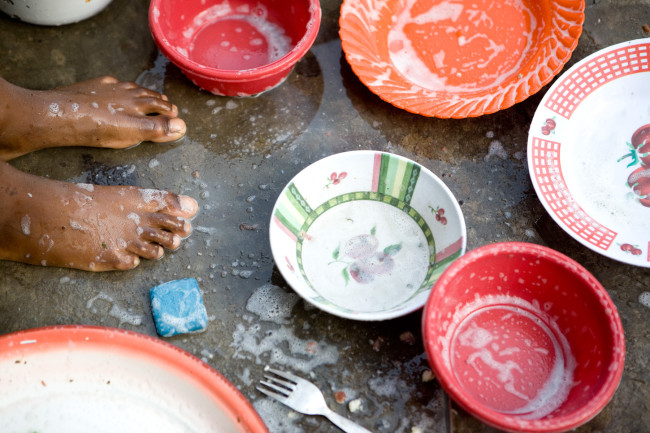 Masengesho does the dishes outside on the ground with a basin of water and a bar of soap.