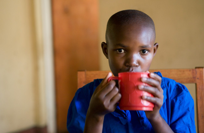 Masengesho drinks her breakfast porridge before school