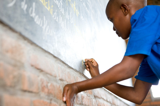 Masengesho answers a question at the chalkboard at her school in Gisenyi, Rwanda.