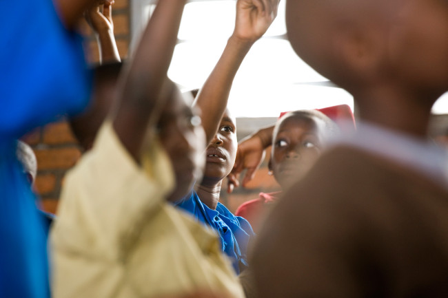 Raising arms for class, Masengesho competes for the right answer with the other students.