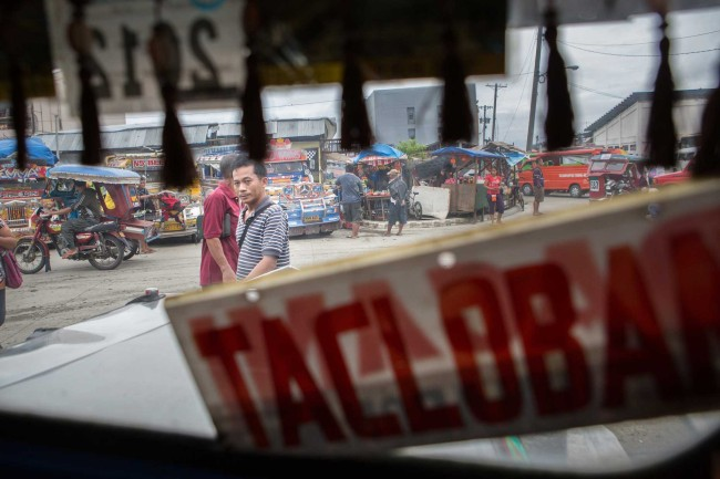 Tacloban, Philippines - A man looks in through the window of a jeepney (local taxi van) that is bound for Guiuan where typhoon relief is still much needed.