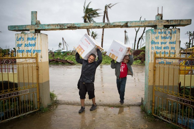 Doc Tiger Girrado helps Astherio Blando (Operation Blessing) haul educational supplies for an elementary school trying to reestablish classes in the devastated area.
