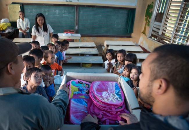 Children receive much needed educational supplies from Doc Tiger and Astherio Blando (Operation Blessing) as part of efforts to reestablish classes in the devastated area.