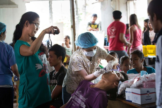 Guiuan, E. Samar, Philippines - Working with a team of volunteer dentists, Dr. Kelly Yangco and others perform 75 extractions in a single shift at a makeshift clinic in Barangay Barbo.
