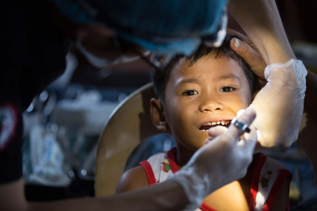 Guiuan, E. Samar, Philippines - Working with a team of volunteer dentists, Dr. Atom Kobayashi helps to perform 75 extractions in a single shift at a makeshift clinic in Barangay Barbo.
